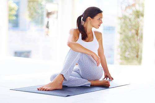 Ardha Matsyendrasana - Young woman practising yoga exercise